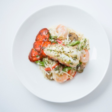Lobster and Shrimp Risotto: Broiled Maine lobster tail served over risotto with shrimp, mushrooms, asparagus, roasted red peppers, basil and Parmesan