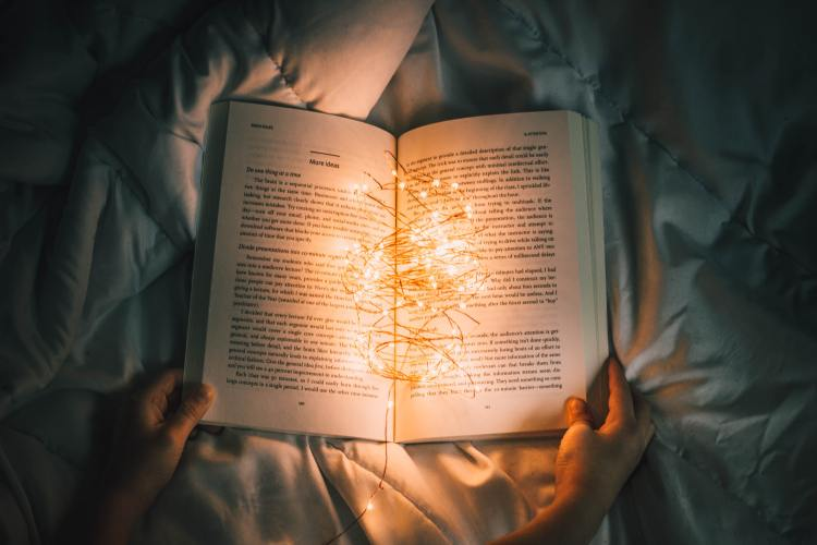 Person reading in the dark with cute lights on book